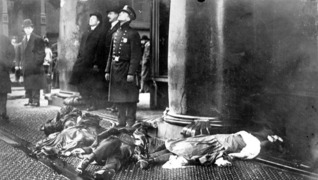 Police officer with bodies of triangle fire victims at feet looking up at workers poised to jump from the upper floors of the burning asch building