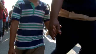 Seg immigrant family holding hands